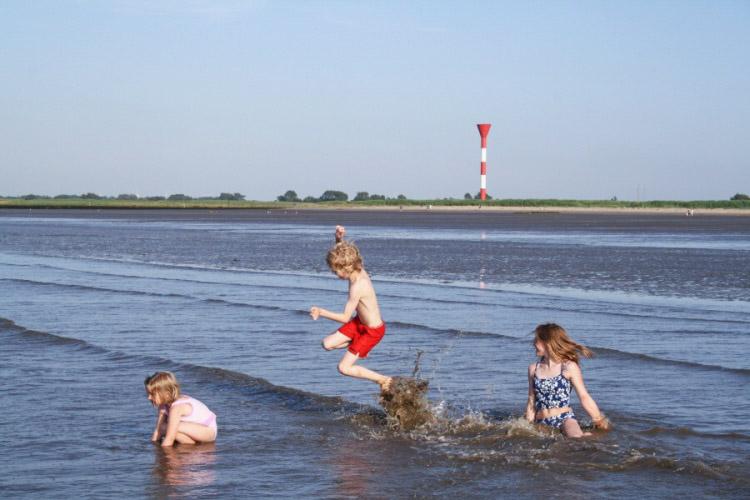 Kinder spielen in der Elbe bei Otterndorf